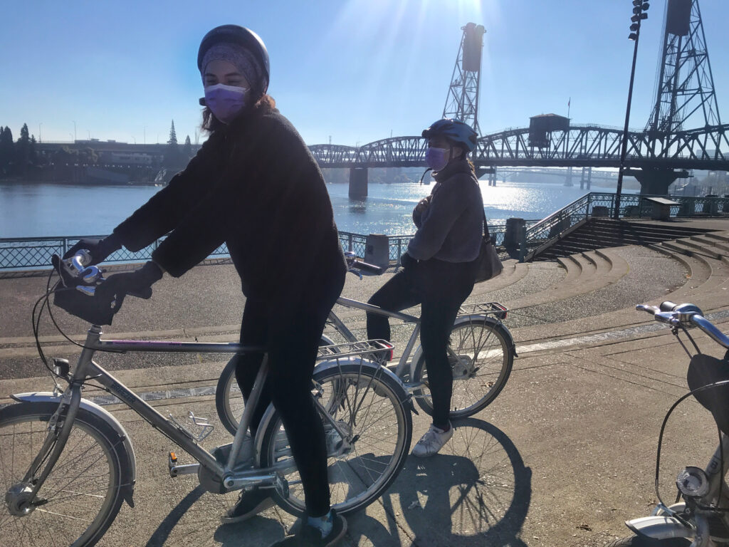 two young Black women on silver bikes smile behind their masks on a sunny day, Hawthorne Bridge in the background and Willamette River shining in the sun