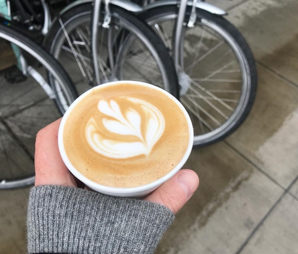 a beautiful cup of coffee with latte art held in a hand wearing a grey sweater in front of silver bikes